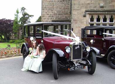 Vintage Wedding Car with 2 pretty young bridesmaids sat on the side of a  1920's Austin 12 in the saloon design.